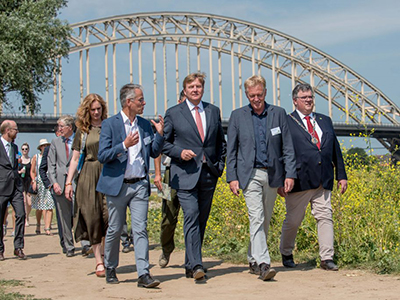 King Willem-Alexander (middle) is guided by Frans Schepers (right) and Professor Hans de Kroon (left) during a short walk on the floodplains of the River Waal. On the far left is Mrs. Harriet Tiemens (Nijmegen Municipal Council) and on the far right Mr. Hubert Bruls, Mayor of Nijmegen. (Image: Marscha van Druuten)