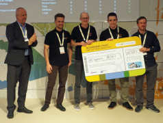 Die Gewinner des NXP Cup 2019 bekamen von Rolf Nissen (links, NXP) ein Flugticket überreicht. Bild: Elektor / TS