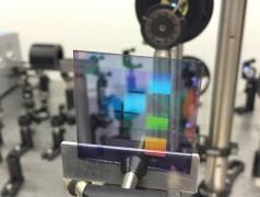 Ein Werkstück des neuen Lasermaterials mit zehn Quadraten, jeweils mit einem anderen Muster von Silberstreifen. Die Farben auf dem Testmuster sind nicht das Laserlicht (der Laser ist auf diesem Foto nicht eingeschaltet), sondern Spiegelungen wie auf einer CD (Foto: Alexei Halpin, TU Eindhoven).