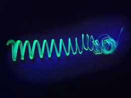 Geëxtrudeerde spiraal van kunststofomhulde silicium-nanoblaadjes in UV-licht (foto: Tobias Helbich / TUM).