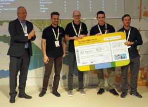 De winnaars van de NXP-Cup 2019 kregen van Rolf Nissen (links, NXP) een vliegticket overhandigd. Afbeelding: Elektor / TS