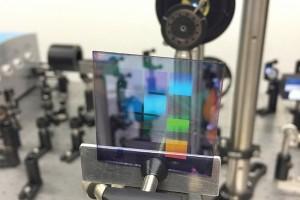 Een proefstuk van het nieuwe lasermateriaal. Het bevat tien vierkantjes met daarin telkens een ander patroon van zilverstippen. De zichtbare kleuren op het proefstuk zijn niet het laserlicht (de laser is niet aan op deze foto), maar zijn reflecties net als bij een CD (foto: Alexei Halpin, TU Eindhoven).