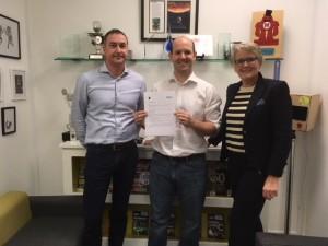 Eben Upton van de Raspberry Pi Foundation met de MagPi-overeenkomst, geflankeerd door Ferdinand te Walvaart en Margriet Debeij van Elektor.