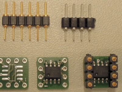 Different stages of the adapter 150797-1 v1.0 and three kind of useable pin headers