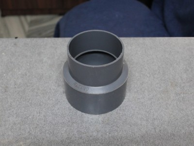 A 4 inch to 3 inch PVC reducer is used