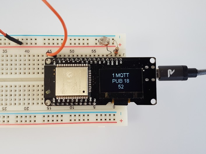 The OLED shows the latest measured value and MQTT status.