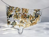A newly developed flexible, biodegradable semiconductor developed by Stanford engineers shown on a human hair. Image credit: Bao lab.