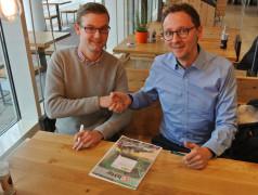 Udo Bormann (Elektor, links) und Matthias Wilkens (NXP) beschließen die Zusammenarbeit beim NXP-Cup für europäische Schulen und Universitäten mit einem Vertrag und einem Handschlag.